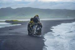 Rock outcrop on black volcanic sand, near Vik, Iceland Stock Photos
