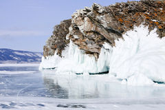 Rock over ice. Rock covered with icicles over frozen water Royalty Free Stock Photography