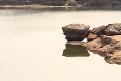 Rock over water. And its reflection in khong river Royalty Free Stock Image