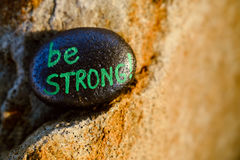 A rock painted black with the message Be STRONG Stock Image