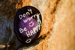 A rock painted black and purple stating Don't worry be happy Stock Photos