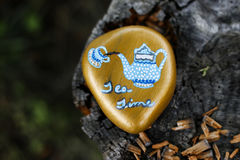 Rock painted gold with blue and white teapot pouring tea into a teacup Stock Image