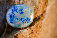 A rock painted silver and light blue stating Be Brave. A rock painted silver and light blue with the words & Be Brave painted in blue. Rock is designed to be royalty free stock image