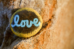 A rock painted yellow with the word love written. A rock painted yellow and light blue, dotted letters  with the word & x22;love.& x22;  Rock is designed to be Stock Images