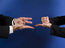 Rock, paper, scissors. Two business people playing a game in order to make a decision Stock Images