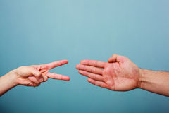 Rock paper scissors. Young men and women are playing rock paper scissors Royalty Free Stock Photo