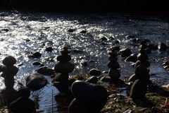 Rock people at river`s edge with sunlight sparkling on the water Stock Photos