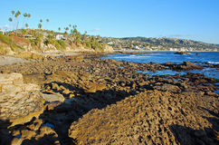 Rock Pile at low tide with Laguna Beach and Heisler Park in the background. Expansive view of Rock Pile Beach, California at extreme low tide. Picturesque stock images