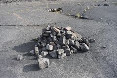 Rock pile marking a trail along a desolate stone backdrop royalty free stock photography