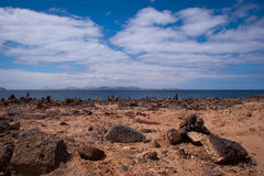Rock piles in playa blanca. Stone piles in playa blanca with fuerteventura in background Royalty Free Stock Images