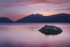 Rock with a Pink Sunset and Lake Stock Photography