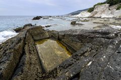 Rock pool with rushing water and seaweed Royalty Free Stock Photo