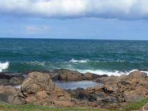 Rock pool and sea. Scenic view of rock pool on coastline with cloudscape over sea Royalty Free Stock Photography