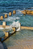 Rock pool by the sea. Picture of a rock pool taken at Coogee Beach in Sydney Australia.  The waves of the ocean splash against the concrete looking pool Stock Images