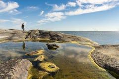 Rock pool and woman Huvudskär Stockholm archipelago stock photography