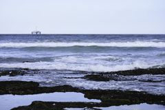 Rock Pools On Sea Shore With Ocean Horizon And Oil Drilling Platform In The Distance royalty free stock photo