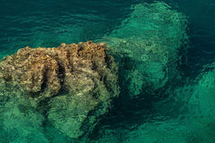 The rock rises from a seabed. Gradient color from turquoise seawater to light brown rocky seabed. Photo was taken at an angle of 60 degrees to the horizon Royalty Free Stock Photo
