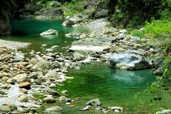 Rock and river. Silence water reflect a green color and white rock make it to an balance picture Royalty Free Stock Photography
