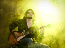 Rock and roll. A man playing electric guitar in yellow smoke Royalty Free Stock Photo