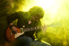 Rock and roll. A man playing guitar sitting on a stage in yellow smoke Royalty Free Stock Photography