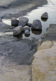 Rock and roll. Rounds rocks sit on top of flat rocks and water Stock Images