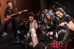 Rock and roll band sitting together and drinking beer after concert on stage Stock Photography