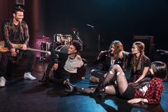 Rock and roll band sitting together and drinking beer after concert on stage Stock Images