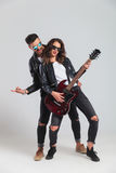 Rock and roll couple playing electric guitar and scream Stock Photography