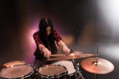 Rock and roll dziewczyna bawić się hard rock muzykę z bębenami ustawiającymi Zdjęcia Stock