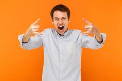 Rock and roll! Expressive man showing rock hand at camera and sh Stock Photography