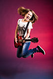 Rock and Roll girl. Portrait of young girl with a guitar on the stage Stock Photo