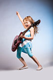 Rock and Roll girl. Portrait of young girl with a guitar on the stage Royalty Free Stock Images