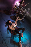 Rock and roll girl lying on stage and playing hard rock music with bass guitar Stock Photo