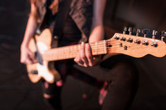 Rock and roll girl playing bass guitar on stage. Cropped shot of rock and roll girl playing bass guitar on stage Royalty Free Stock Images