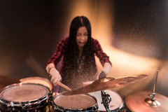 Rock and roll girl playing hard rock music with drums set. Rock and roll young girl playing hard rock music with drums set Stock Photos