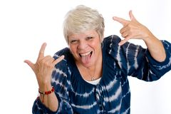 Rock and Roll Grandma. A gray haired mature woman giving a rock and roll sign while sticking her tongue out Royalty Free Stock Image