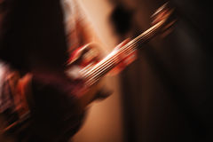 Rock and roll live music background. Blurred electric guitar player on a stage with motion blur effect Stock Image