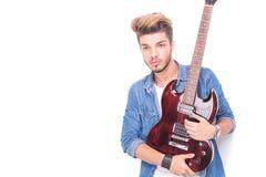 Rock and roll mężczyzna trzyma gitarę i spojrzenia oddalonymi Obraz Stock