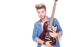 Rock and roll  man holding a  guitar and looks away Stock Image