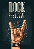 Rock and Roll sign. Vector black vintage engraved illustration. Rock and Roll sign. Hand with metal spiked bracelet giving the devil horns gesture. Vector color Stock Photography