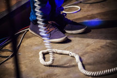 Rock and roll theme. Feet of bass guitar player. On a stage with white wire. Selective focus Royalty Free Stock Photo
