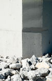 Rock rubble by corners of smooth vertical wall. Stock Photography