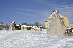 The rock ruins and the snow under the blue sky Stock Images