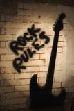 Rock rules with guitar shadow. Guitar shadow with black Rock Rules sprayed on wall in background Royalty Free Stock Image