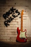 Rock rules with red guitar. Red Fender copy guitar with black Rock Rules sprayed on wall in background Royalty Free Stock Images