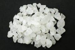 Rock Salt. Macro shot of salt rocks on a black plate stock photo
