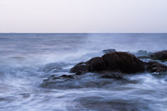 Rock and Sea. The sea surface is smooth like silk in the morning Royalty Free Stock Photography