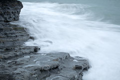 The rock and the sea. Foam of the waves crashing against the rocks Stock Image
