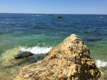 A rock on the sea in Algarve in Portugal stock images