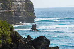 Rock in the sea. Bali, Indonesia. Rock in the sea against the background of cliffs. Bali, Indonesia Stock Images